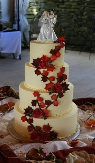 Branches of hand-made sugar fall leaves on smooth buttercream tiers.....
