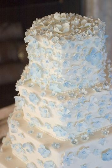 Hundreds of tiny blue sugar blossoms lightly covering buttercream tiers....