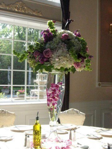 HYDRANGEAS, ROSES,ORCHIDS, BELLS OF IRELAND AND MINI-CALLA LILLIES ADORN THIS EXTRAORDINARY...