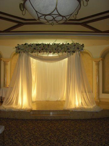 MAGNIFICENT DRAPED CHUPPAH WITH A FULL FLOWERED TOPPER AND WIDE DRAPED TAFETTA AND ORGANZA TO THE...