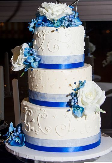 3 tier cake with two shades of blue ribbon with scroll and quilt designs
