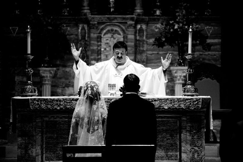 Priest raising heaven and earth at church ceremony.
