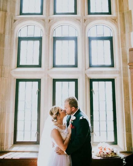 Newlyweds kiss by the windows