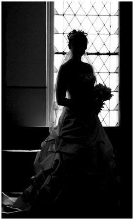Bride waits for the ceremony to begin, glancing out the church window.