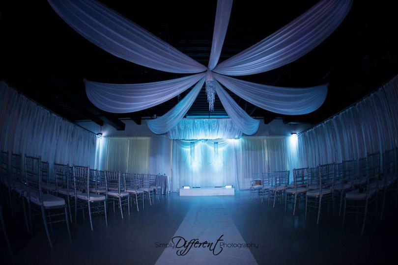 Custom ceiling draping, backdrop, and canopy in white chiffon with decorative strings of crystal...