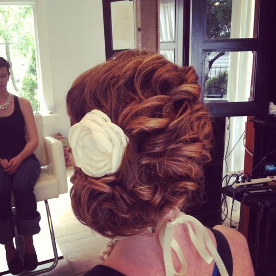 Curled wedding updo with white flower