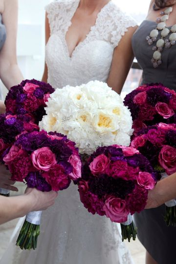 All white for the bride.  Fuchsia and purple for the bridesmaids.  All bouquets consisted of roses...