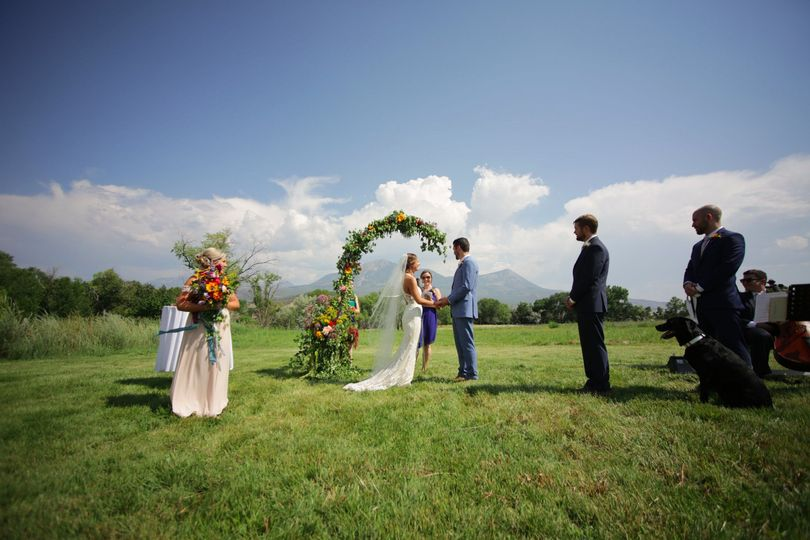 Outdoor ceremony with flower arch