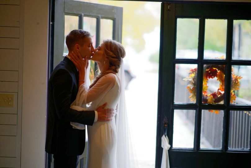 Couple kissing beside a cracked door