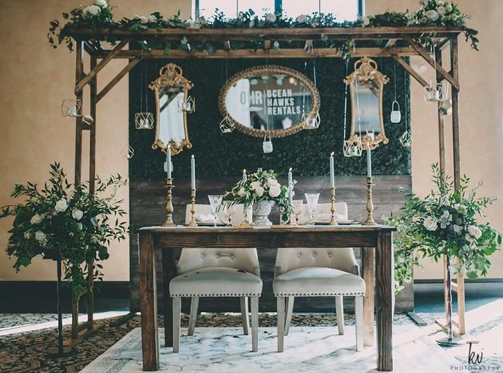 Our sweetheart farm wood table and custom overhang with our hedge wall backdrop!