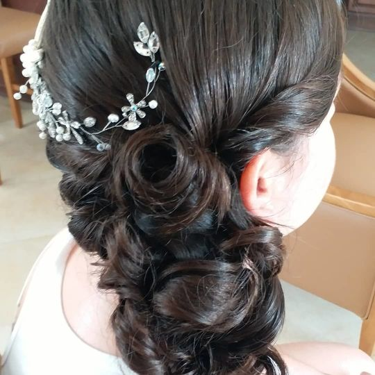 Side swept hair curls with silver hair ornament