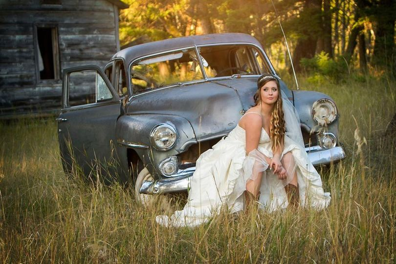Beautiful bride sitting on an old junked car in Kamloops, British Columbia