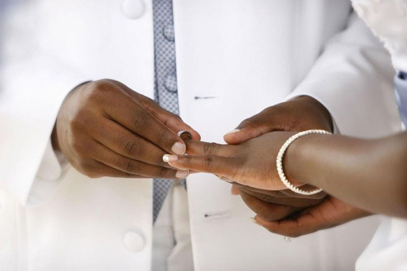 Groom places the ring on Brides hand in Pensacola, Florida