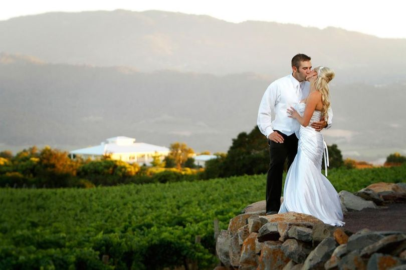 Bride and Groom kissing with a view of David Arthur Vineyards in Calistoga, California