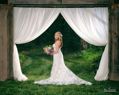 Bride under wedding arch