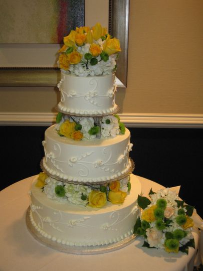 Yellow and green flowers carry the wedding theme onto the wedding cake.