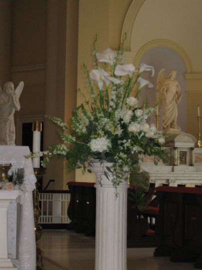 Classic altar pieces are designed with calla lilies, roses, orchids, snapdragons and larkspur.