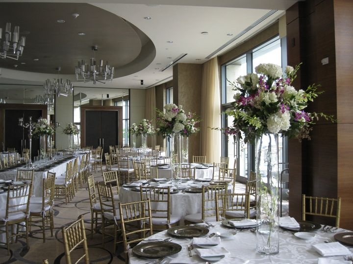 We love doing this high-top centerpieces filled with hydrangea, roses, orchids and cascading...
