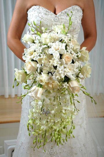 Lavish cascade bridal bouquet featuring all white flowers including roses, gardenias, dendrobium...