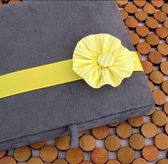 Bright yellow and stone gray wedding invitation served up in a fabric box featuring a hand-sewn...