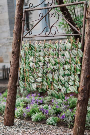 magnolia leaves as escort cards with gold calligraphy on the sentimental gate built into a...