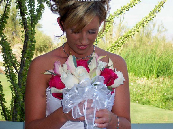 Beautiful bride looking at her bouquet, music and videography for her wedding provided by Desert...