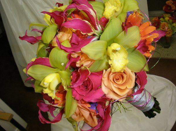 Bright fun bouquet of gloriosa lilies, cymbidium orchids, gerbera daisies, and roses.
