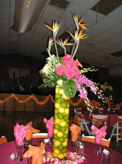 Reception centerpiece of tropical flowers accented with vase full of lemons and limes.