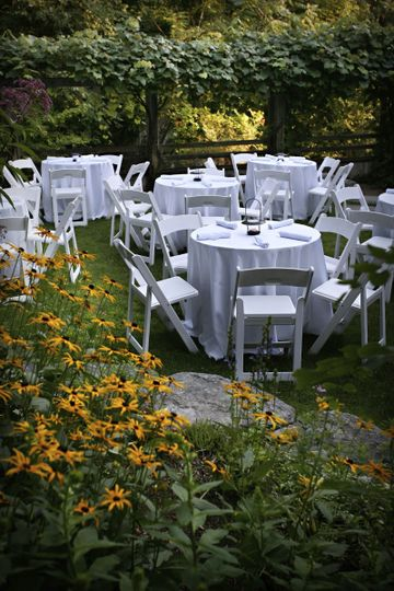 Outdoor dinner seating in our garden, ringed by concord grape arbors and Freeman Brook.