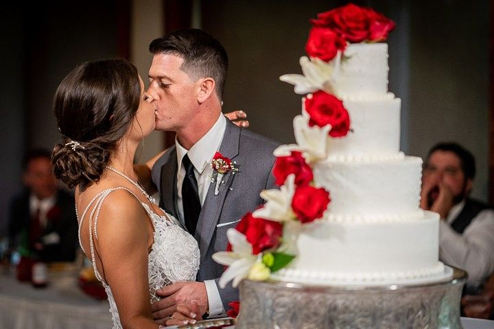 Couple kissing beside wedding cake