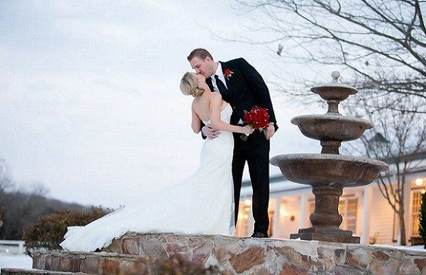 Newlyweds kissing by the fountain