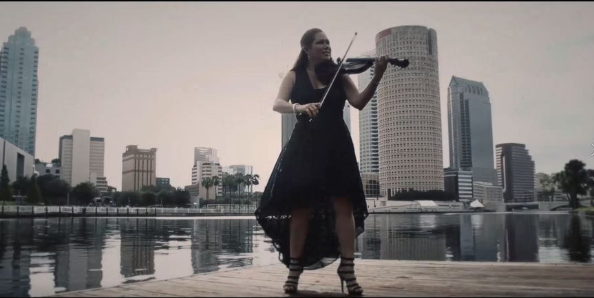 Electric violin being played in front of the cityscape