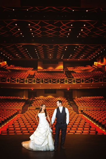 DCP wedding couple on stage alone in large theatre.