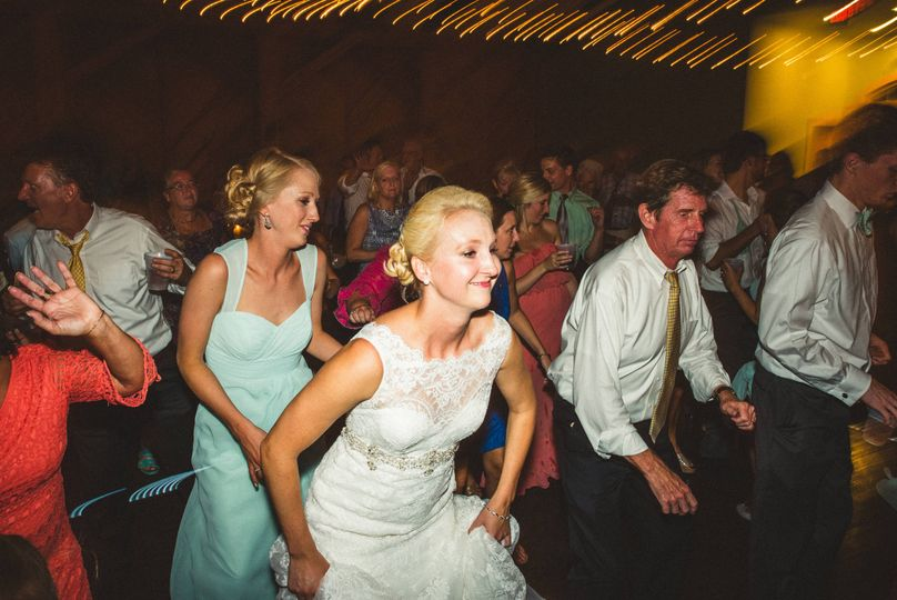Newlyweds and guests line dancing