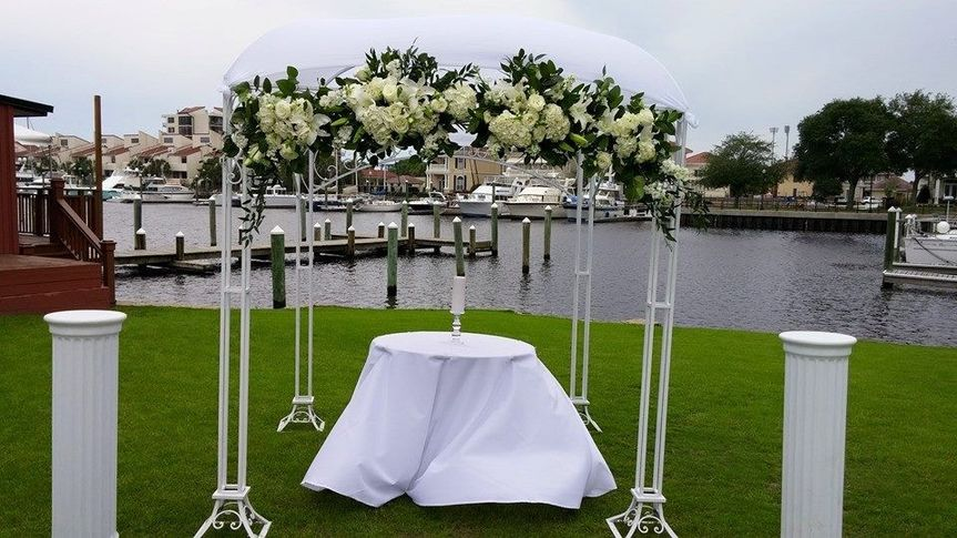 White metal arbor with chuppah and flowers