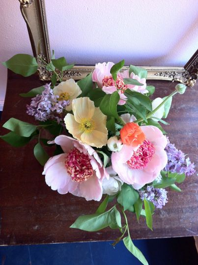 // table centerpiece of peonies, lilac, ranunculus and icelandic poppies