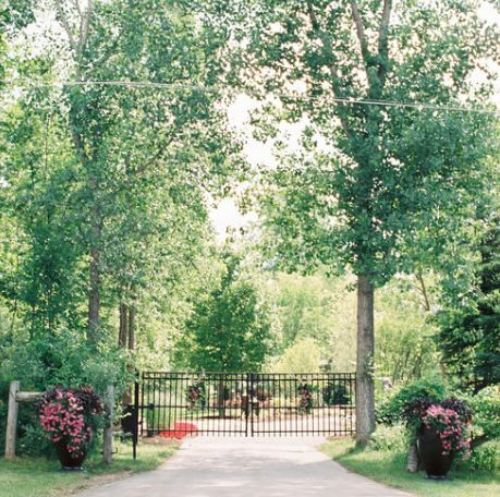 "The entry gates to very private wedding venue, ""Cushing Field House""."
