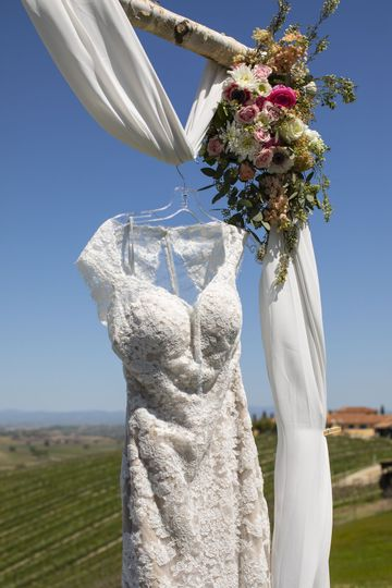 Wedding dress hanging from arbor