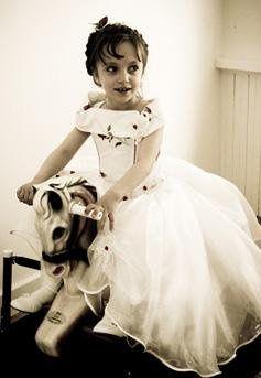 Flower girl riding antique horse.