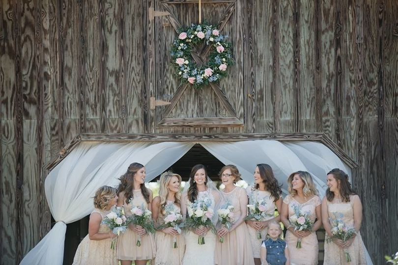 Bride and bridesmaids by the barn entrance