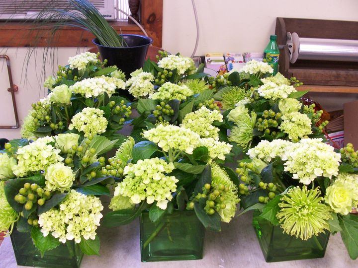 Centerpieces of fuji mums, roses, hydrangeas & hypericum in green glass cubes.