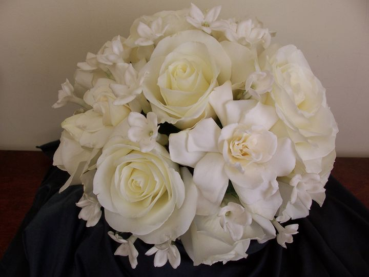 White roses, gardenias and stephanotis in a hand tied bouquet.