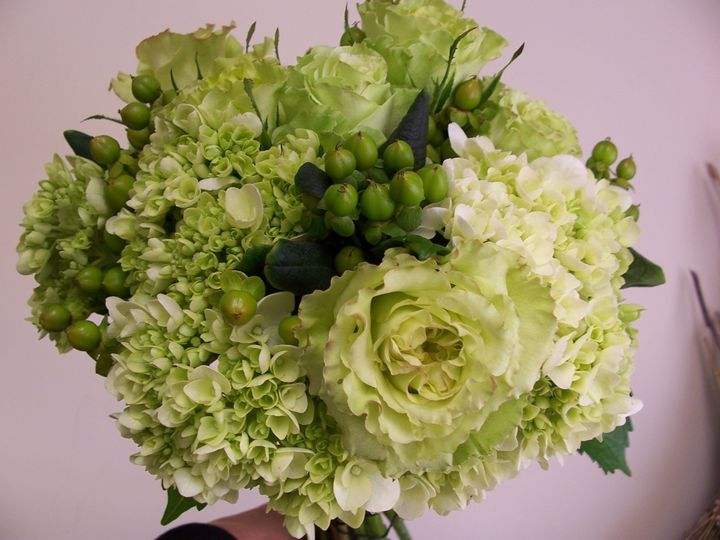 Green hydrangeas, roses and hypericum in a hand tied bouquet.