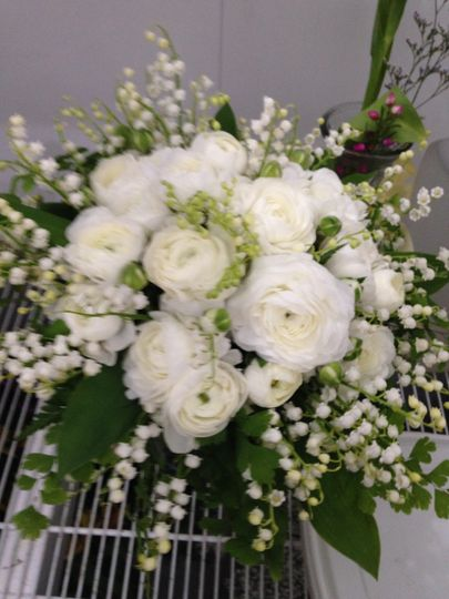 White ranunculus with Lily of the Valley in a hand tied bouquet.