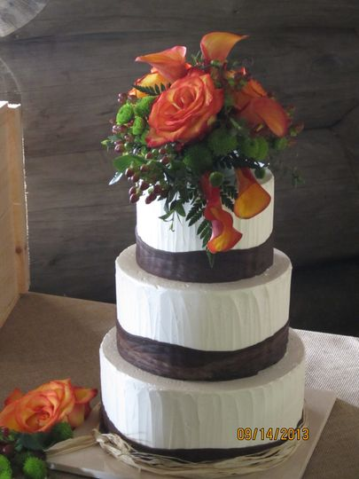 Calla lilies, roses, hypericum and button poms decorate the  cake.