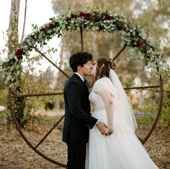 Kiss by the floral circle arch