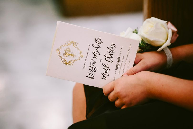 Custom wedding programs with a gold foil stamped monogram for the wedding couple.