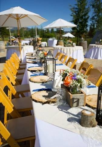 Outdoor rustic event with wood, umbrellas and colorful flowers.