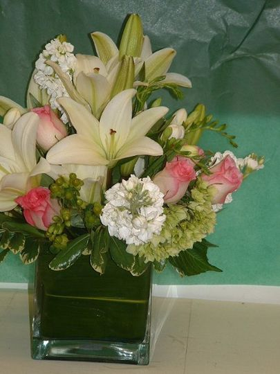 Centerpiece with white lilies, roses & stock.