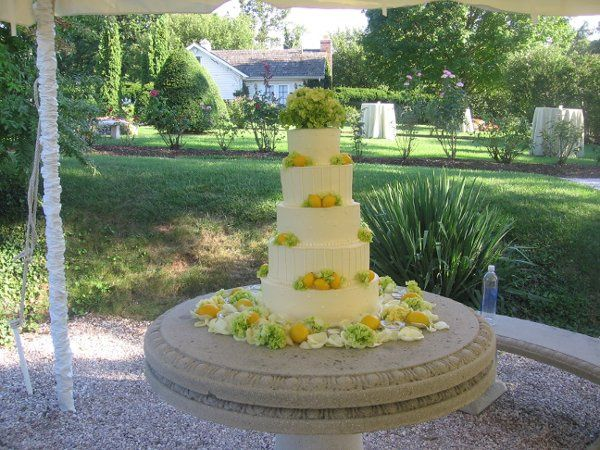 5 tier buttercream cake with vertical stripes, swiss dots, lemons and hydrangeas.
